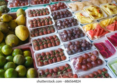 Assorted type of strawberry, grape,pineapple and dragon fruits packed using plastic wrapper at market display.