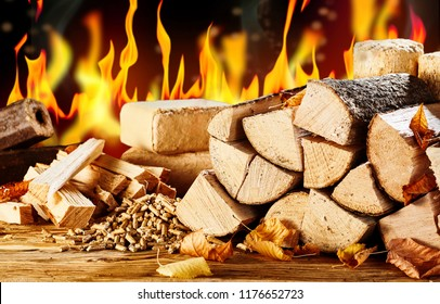 Assorted types of natural biofuels for heating in autumn with split logs, logs and pellets of compressed sawdust and chopped kindling in front of a burning fire
