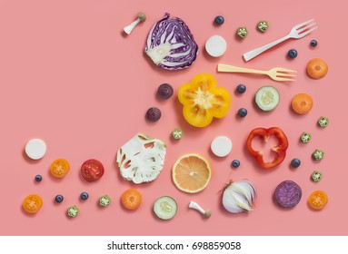 Assorted uncooked sliced vegan food on pink colour background. Flat lay conceptual food still life text space image.