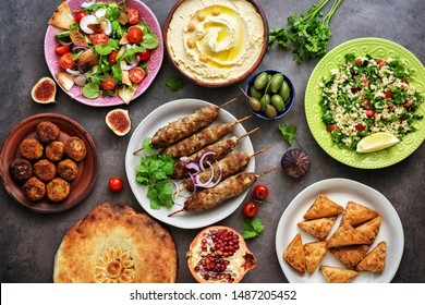 Assorted variety of Arabic and Middle Eastern food on a dark rustic background. Hummus,tabbouleh salad, salad Fattoush,pita,meat kebab,falafel,baklava. Set of Arabian dishes.Top view