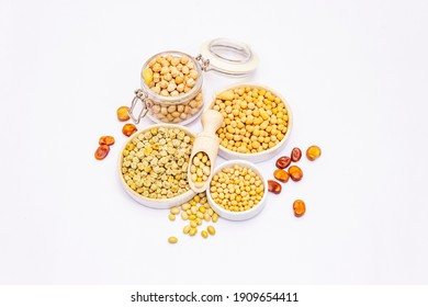 Assorted variety of legumes isolated on white. Chickpeas, soybeans, peas, broad beans in bowls, indispensable ingredients for proper nutrition, top view