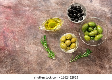Assorted variety of olives in bowls on a dark background. Top view, copy space
