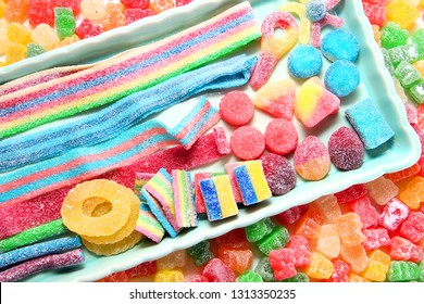 Assorted variety of sour candies includes extreme sour soft fruit chews, keys, tart candy belts and straws. 