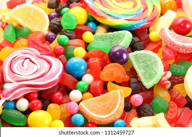 Assorted variety of sweet sugar candies includes lollipops, gummy bears, gum balls and sugar fruit slices. Candy flat lay background.