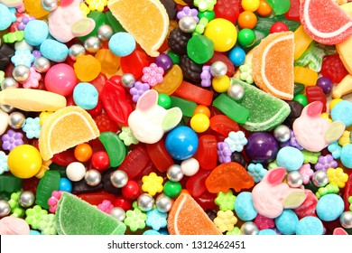 Assorted variety of sweet sugar candies includes gummy bears, Easter bunny candy, gum balls and sugar fruit slices. Candy flat lay background.