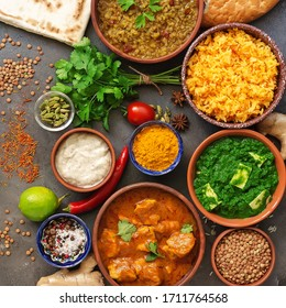 Assorted various Indian food on a dark rustic background. Traditional Indian dishes - Chicken tikka masala, palak paneer, saffron rice, lentil soup, pita bread and spices. Square photo.Top view