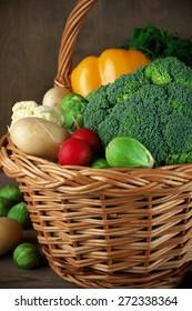 Assorted vegetables in basket on rustic wooden background.