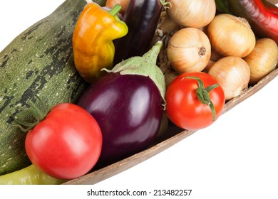 assorted vegetables lying in a wooden scoop isolated on white background