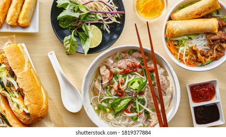 assorted vietnamese dishes with pho, bahn mi, spring rolls in top down composition on dinner table