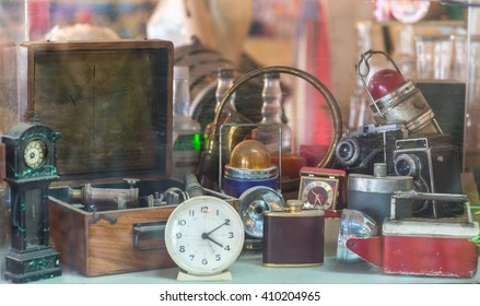 Assorted vintage items, clocks, cameras, flasks, sextant, lamps behind shop window.