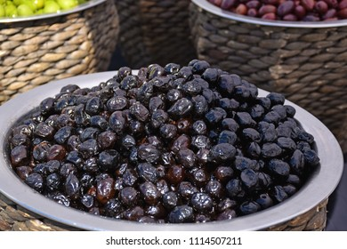 Assorted whole Italian olives (black, green, red) close up. Different marinated olives on provencal street in the Arendal international market, Arendal city, Norway.