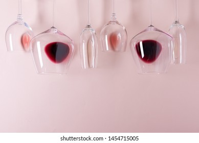 Assorted wineglasses with red, rose and white wine lying top edge on pink background. Wine degustation concept. Flat lay. Top view. Copy space
