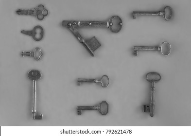 assortment of antique keys in black and white isolated against gray background