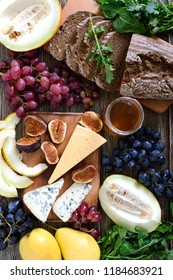 Assortment of appetizer: grapes, cheese, blue cheese, figs, melon, arugula, grain bread, honey on a wooden table Top view.