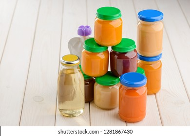 Assortment baby food on wooden table. Stacked jars and pouch of puree, bottle of juice.