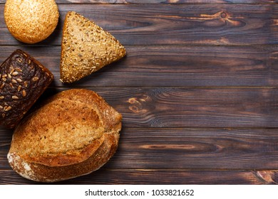 Assortment of baked bread on wooden table background. top view with copy space.