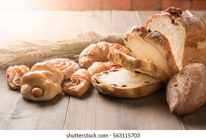 Assortment of baked bread and wheat on wood table background, homemade bakery