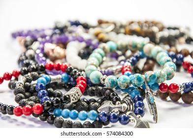 Assortment of woman's bead bracelets closeup isolated on white