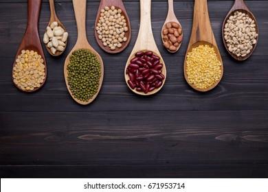 Assortment of beans (Mung bean, Soya bean, Red kidney bean, Navy bean, Peanut) in wooden spoon on dark wooden background, top view