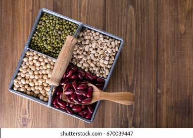 Assortment of Beans, Red kidney bean, Mung bean, Soy bean, and Navy bean on wooden table, top view