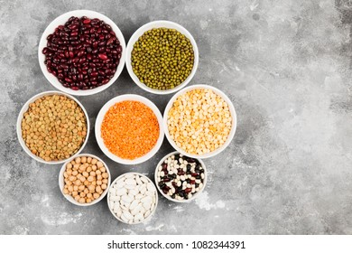 Assortment of beans (red lentil, green lentil, chickpea, peas, red beans, white beans, mix beans, mung bean) on gray background. Top view, copy space. Food background