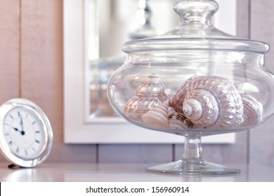 Assortment of beautiful shells in a glass jar reflected in a mirror in the background. Pastel color theme in shades of pink.