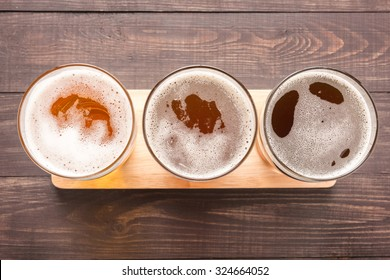 Assortment of beer glasses on a wooden background. Top view.
