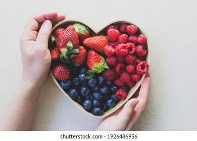 Assortment berries blueberries, strawberries and raspberries in heart woden box. Keto diet, healthy food.