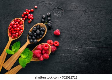 Assortment of berries. Raspberries, blackberries, strawberries, cranberries. On a wooden background. Top view. Free space for text.
