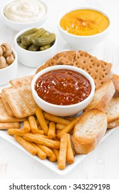 assortment breads, crackers and sauces on white table, vertical