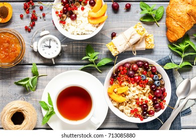 Assortment of breakfast - porridge with berries, cottage cheese, tea, juice, croissant, oat bars and jam. Healthy food. Top view. Flat lay