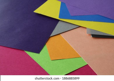 Assortment of bright coloured squre papers randomly scattered