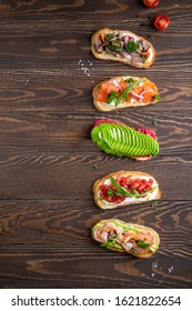 Assortment of bruschettas with fillings of avocado, salmon, cherry tomatoes, basil, cheese, prosciutto, jamon, herbs. On a dark wooden background. top view overhead view copy space