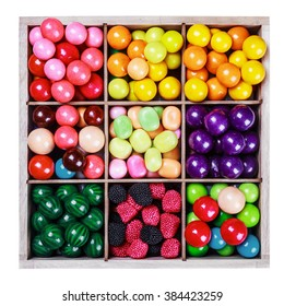 assortment of candy and gum in a wooden box on a white background