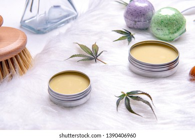 Assortment of cannabis topicals with bath bombs and marijuana salve isolated over white background - cannabis spa concept