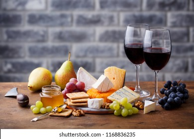 Assortment of cheese, grapes with red wine in glasses. Stone and wood background. Copy space.