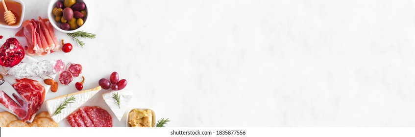 Assortment of cheese and meat appetizers. Overhead view corner border on a white marble banner background with copy space.