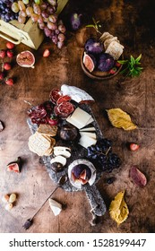 assortment of cheese on wooden board with fruits, honey and ham on brown wooden table, selective focus