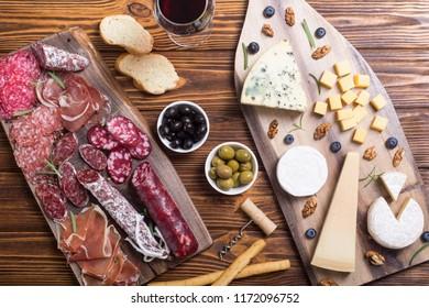 Assortment of cheese and sausages : ham salami jamon camembert brie parmesan .