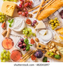 Assortment of cheeses, fruits, breads, wine and snacks on white
