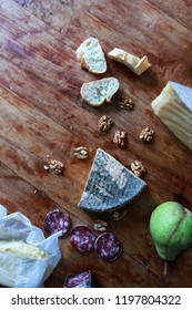 Assortment of cheeses, nuts, butter, dry sausage, pear, baguette on a wooden background. Top view. Space for text