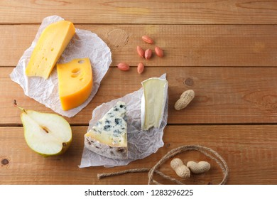 Assortment of cheeses, pears and peanuts on parchment paper. Camembert, hard yellow cheese, dorblu on wooden boards. Dairy products, half pears and nuts