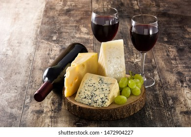 Assortment of cheeses and wine on wooden table