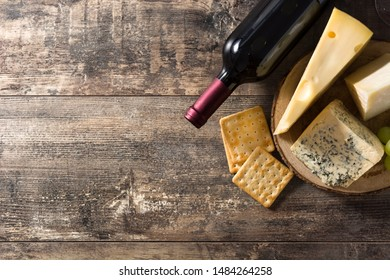 Assortment of cheeses and wine on wooden table. Top view. Copyspace