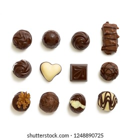 Assortment of chocolate candies from black, milk and white chocolate with nuts and marzipan on the white background