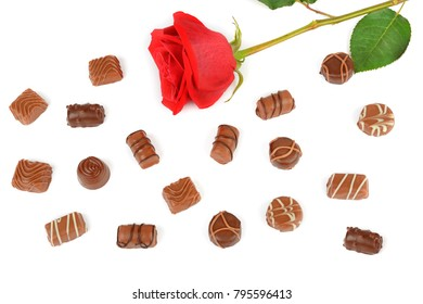 Assortment of chocolate candies and red rose isolated on white background. Flat lay, top view. Free space for text.