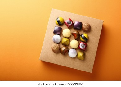 Assortment of chocolate candy on box on orange background, food top view