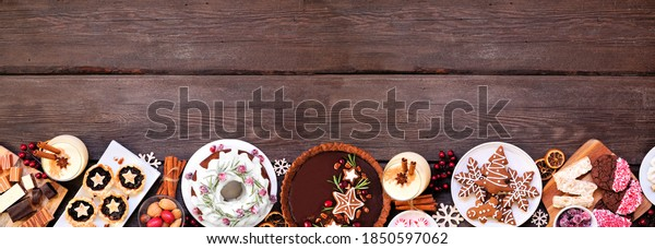 Assortment of Christmas holiday desserts and sweets. Top view bottom border over a wood banner background. Bundt cake, chocolate pie, mincemeat tarts, cookies and eggnog.