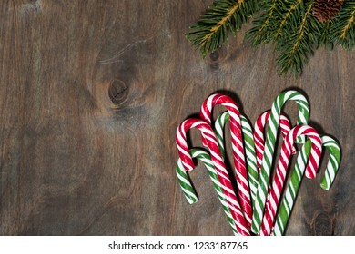 assortment of christmas sugar candies and fir branches on grey background, top view