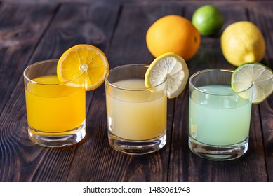 Assortment of citrus juices on the wooden background